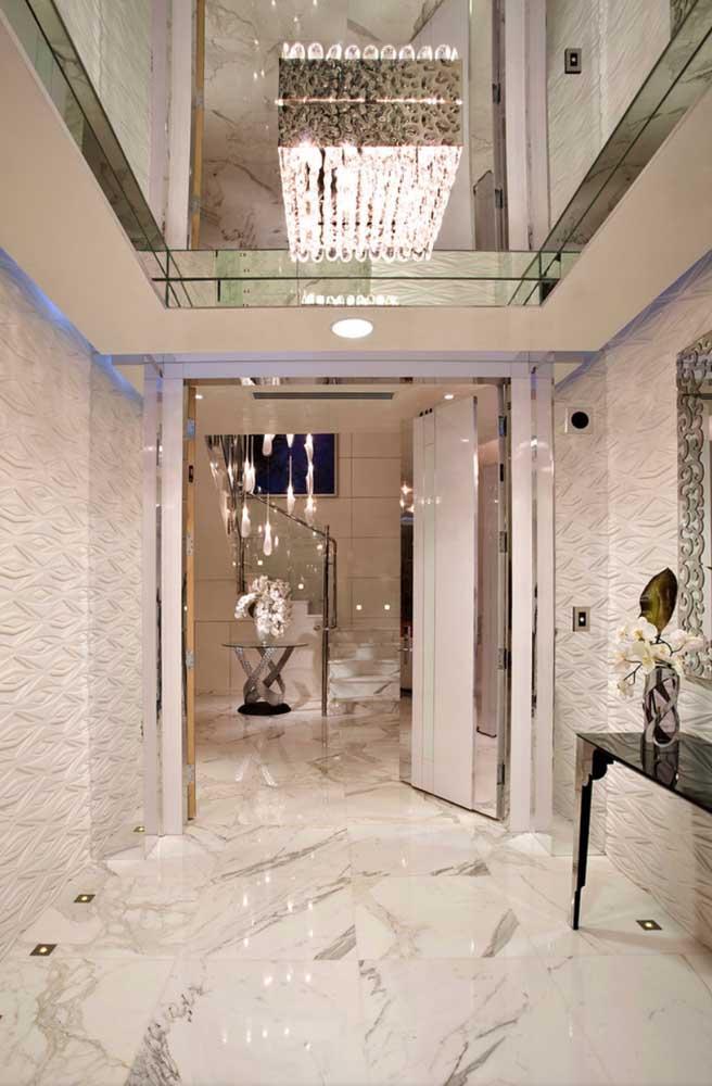 Hall de entrada luxuoso da penthouse. Os destaques ficam para o mármore no chão e o cristal no teto