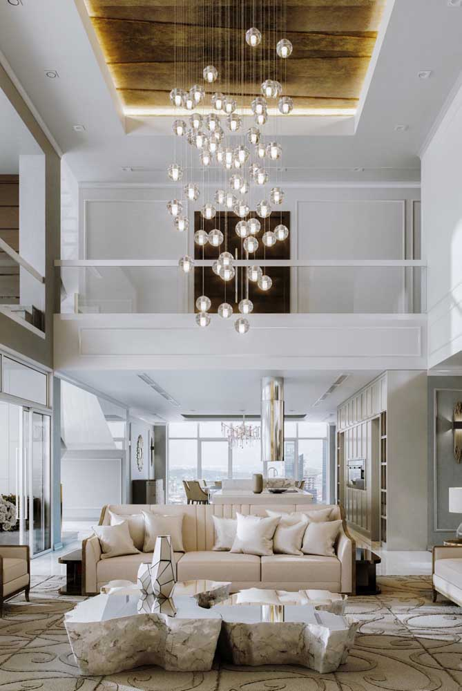 Aqui, o pé direito alto da penthouse foi valorizado pelo lustre de vidro suspenso e pelo detalhe da sanca de gesso no teto