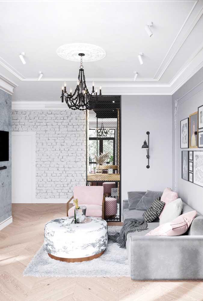 A sala de estar em tons de cinza apostou em uma poltrona cor de rosa combinando com as almofadas