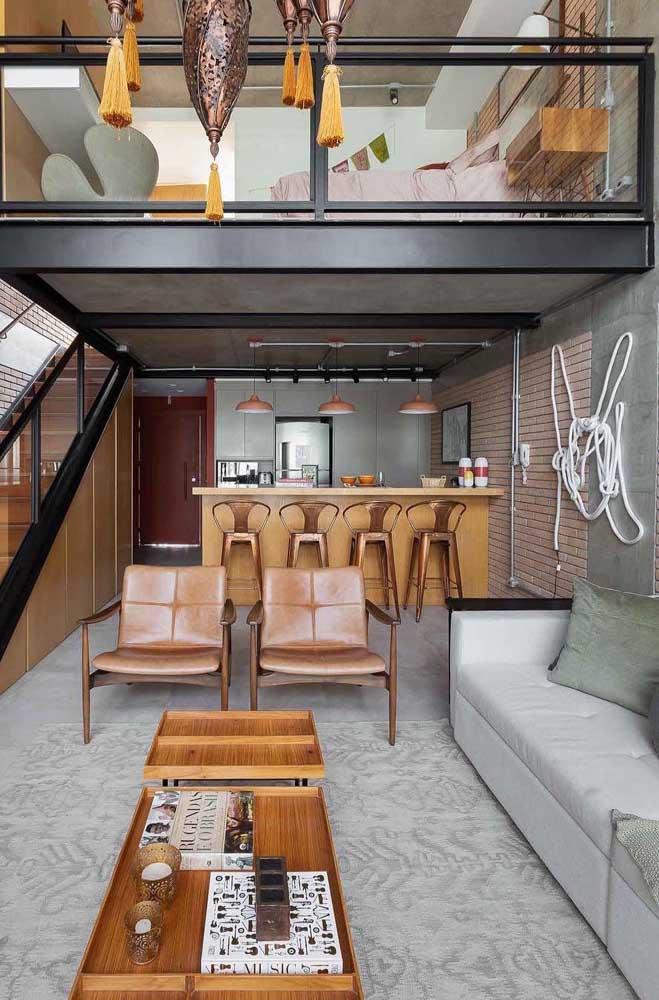 Aqui, as poltronas de couro ajudam a demarcar a área da sala de estar. Esse, inclusive, é um ótimo jeito de delimitar espaços integrados