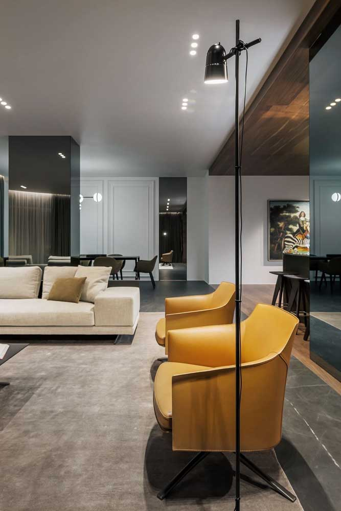 Dupla de poltronas amarelas para a sóbria sala de estar. O formato arredondado deixa as poltronas mais acolhedoras