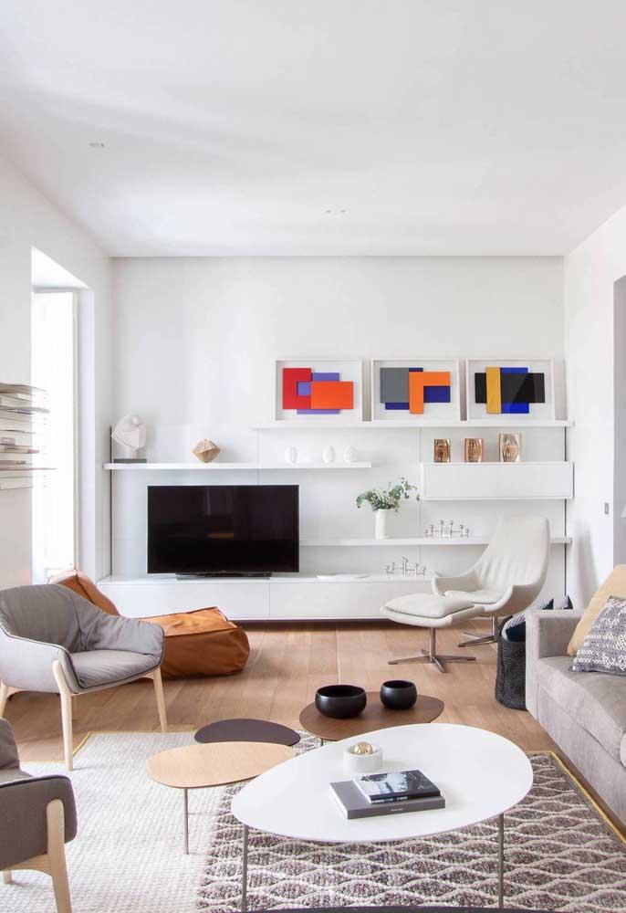 Sala de estar grande decorada com três tipos diferentes de poltrona: uma com apoio para os pés, outra em estilo futon e mais duas com design tradicional