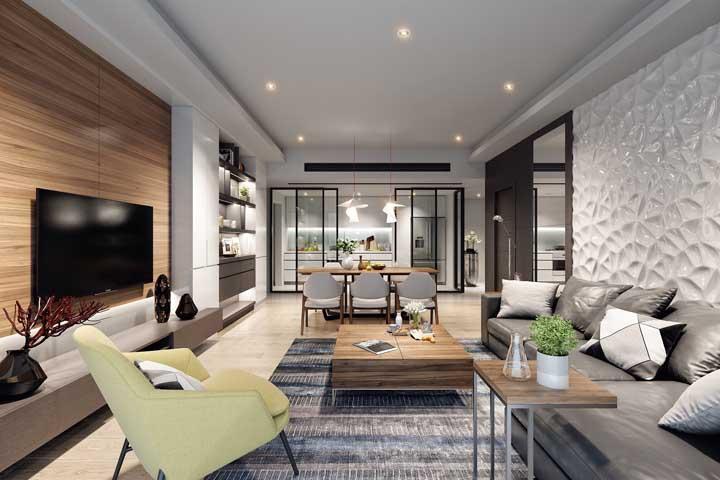 Nessa sala de estar grande, a poltrona ajuda a deixar o espaço mais harmonioso, completo e elegante