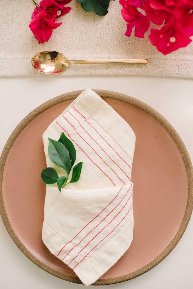Guardanapo de tecido bordado. O tom cru do pano se harmoniza perfeitamente com a proposta rústica da mesa