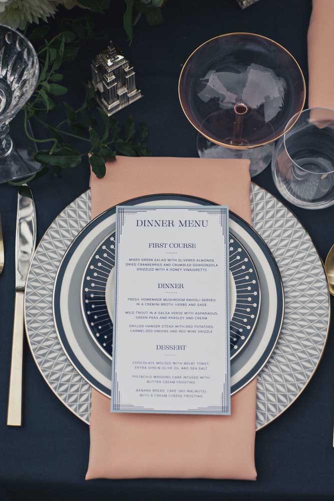 A mesa posta em tons de azul apostou em um guardanapo cor salmão para criar contraste