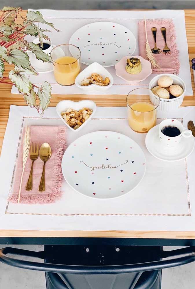 Mesa posta para o café da manhã com guardanapos cor de rosa. Uma graça!