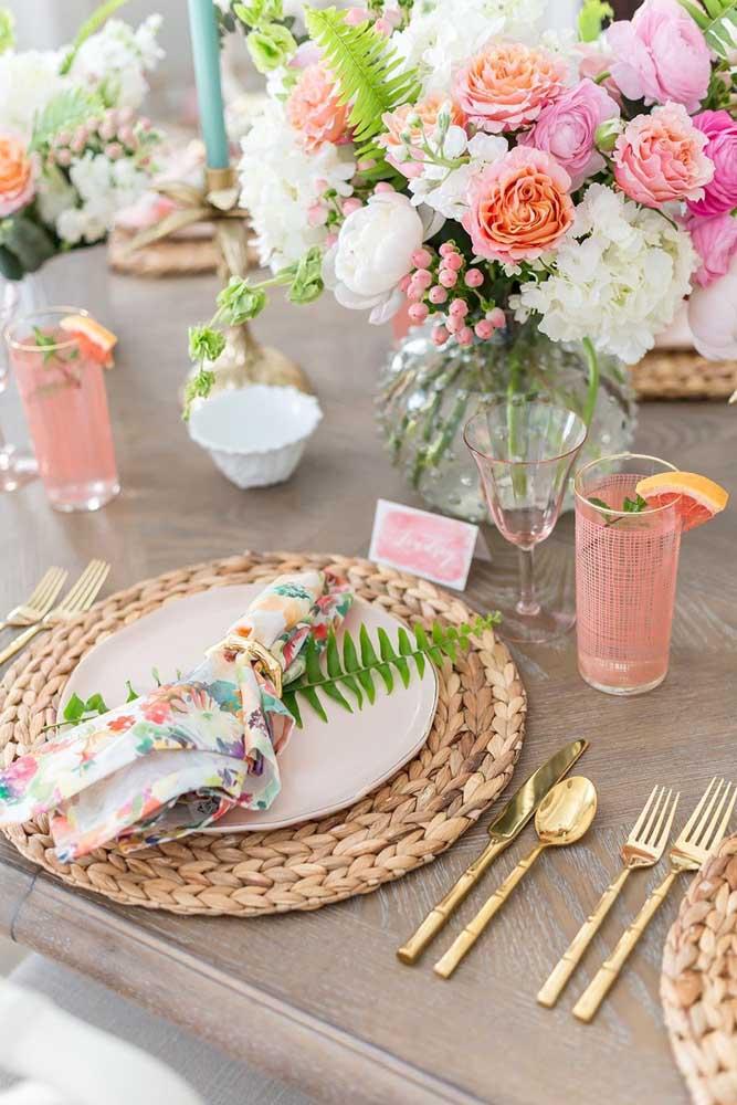 Inspiração de mesa posta tropical com um guardanapo de tecido florido preso pela argola. O detalhe fica por conta do galhinho de samambaia
