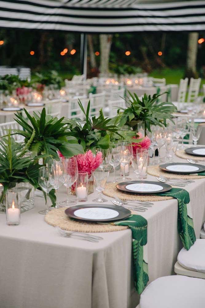 Mesa posta de casamento com guardanapo de tecido estampado de folhas, combinando com os arranjos do centro