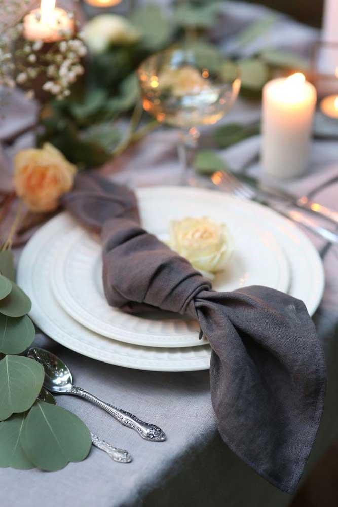 Guardanapo de tecido preto exposto na mesa com um nó, só isso!