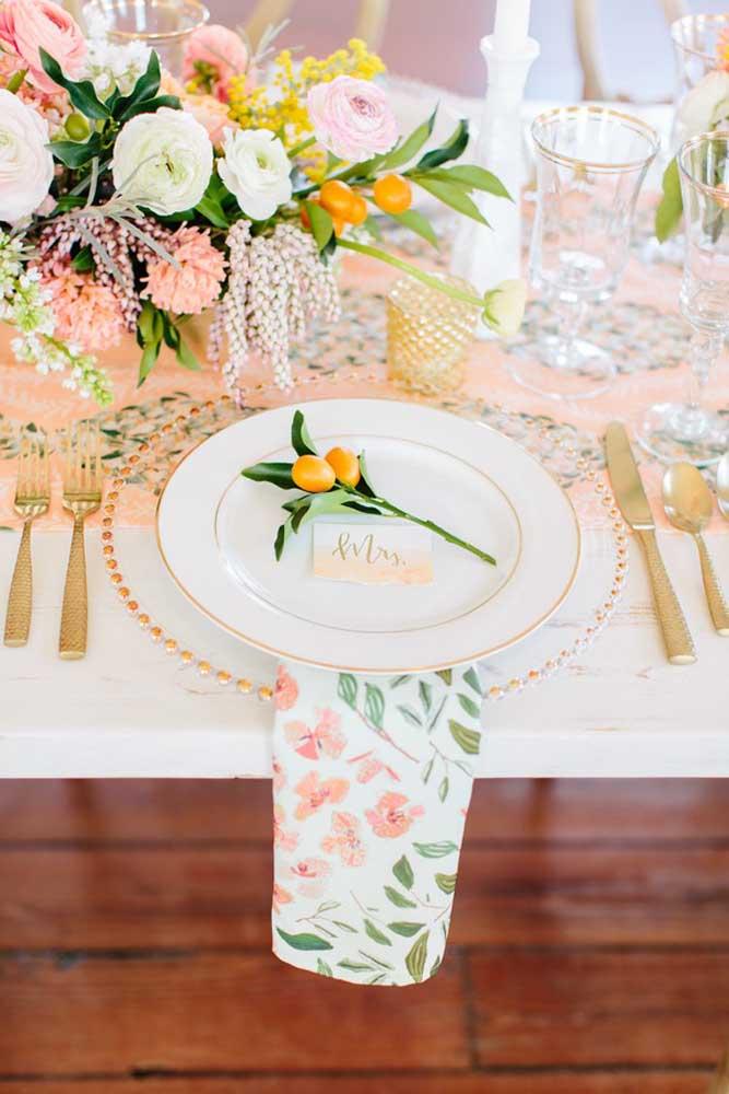 Mesa posta com guardanapo de tecido floral disposto sob o prato