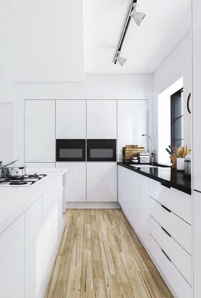 Cozinha grande e branca. Repare que aqui os estilos moderno e minimalista predominam, resultando em uma cozinha simples, mas de muito bom gosto