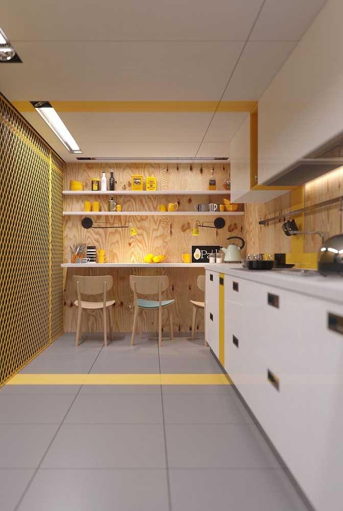 O recorte amarelo no teto traz despojamento e jovialidade para a cozinha grande