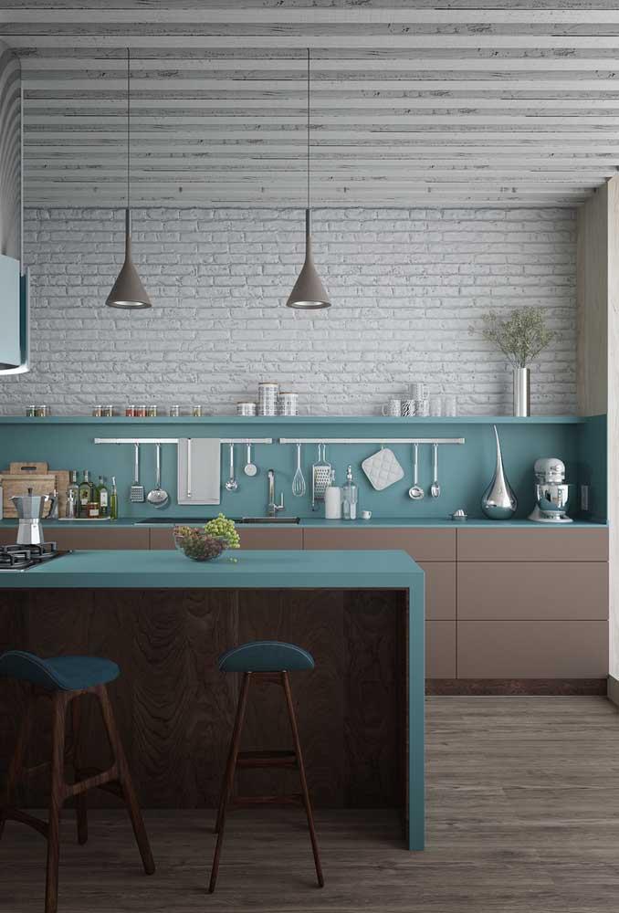 Cozinha grande moderna em tons de azul, branco e marrom. O balcão com cooktop faz a integração com os demais ambientes