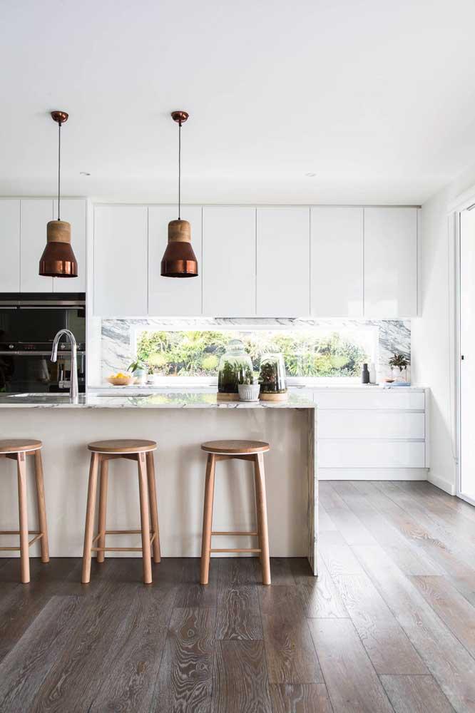 O piso de madeira deixa a cozinha grande mais aconchegante