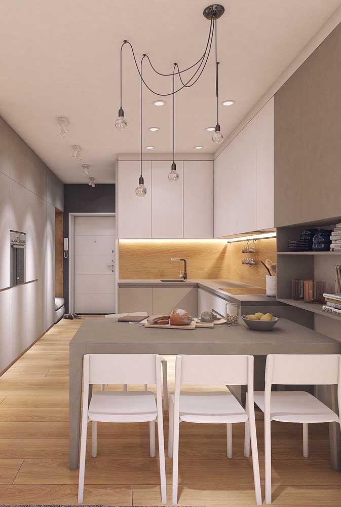 Cozinha grande em L com balcão. A iluminação difusa é o grande destaque por aqui