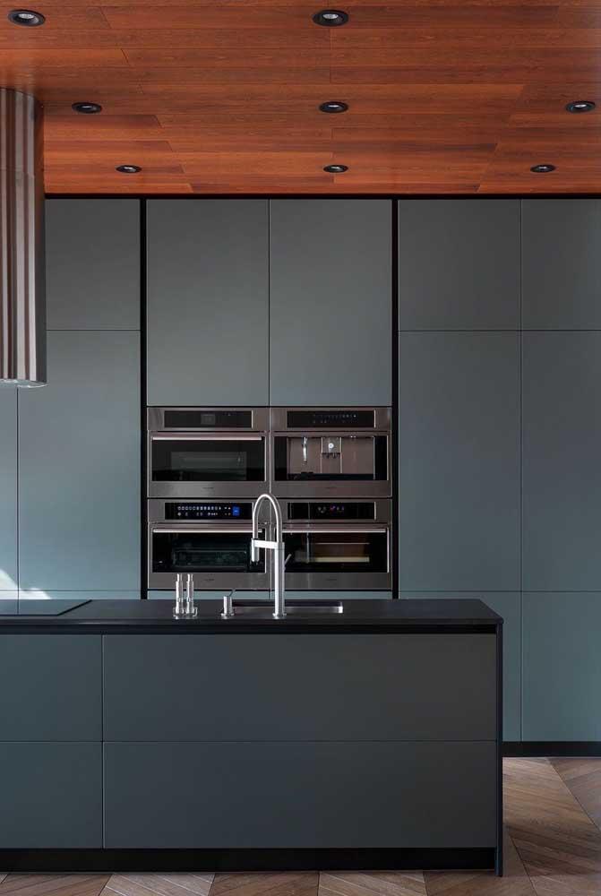 Cozinha grande moderna com forro de madeira, armários azuis e eletros de inox