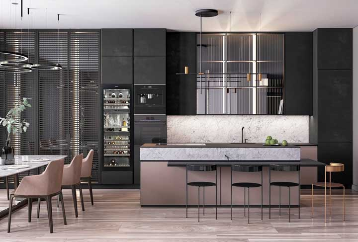 Cozinha grande de luxo com direito a adega climatizada para as bebidas e uma elegante combinação entre o tom de rosé, o preto e o dourado