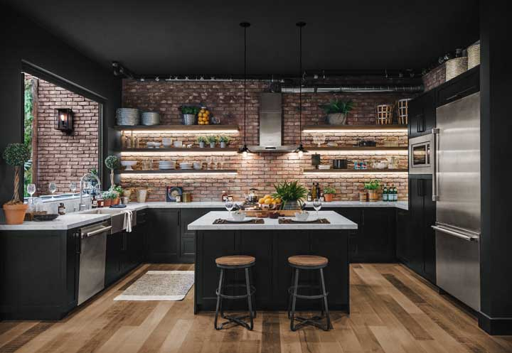 Cozinha grande em estilo rústico e moderno. A ilha que funciona como balcão é um charme a parte e ainda resolve muito bem o espaço do ambiente