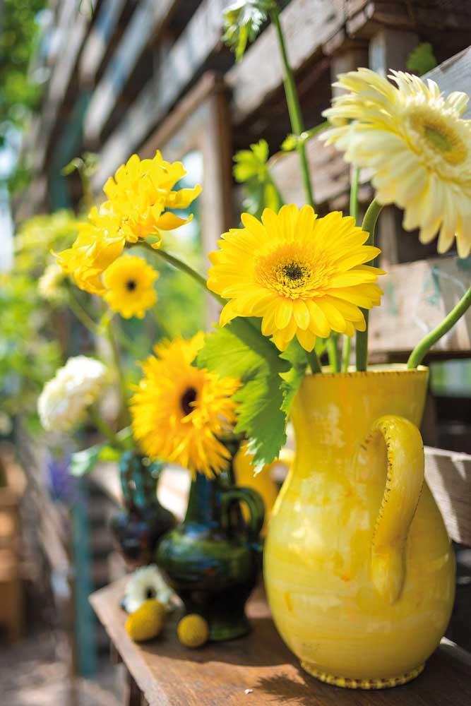 Arranjo despretensioso de gérberas amarelas no jarro que virou vaso. Um deleite para quem aprecia decorações rústicas e acolhedoras