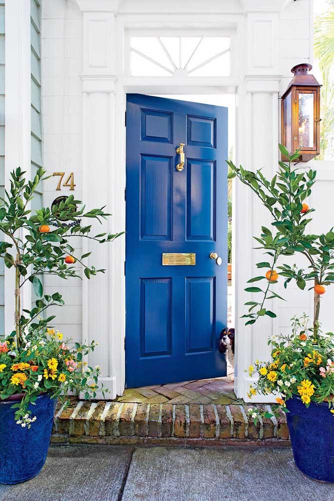 A entrada da casa ganhou a presença de gérberas amarelas no vaso contrastando lindamente com a porta azul royal