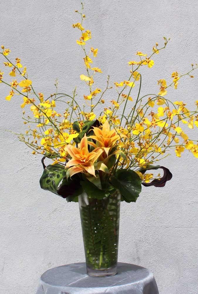 Arranjo tropical e alegre feito com orquídeas chuva de ouro e bromélias
