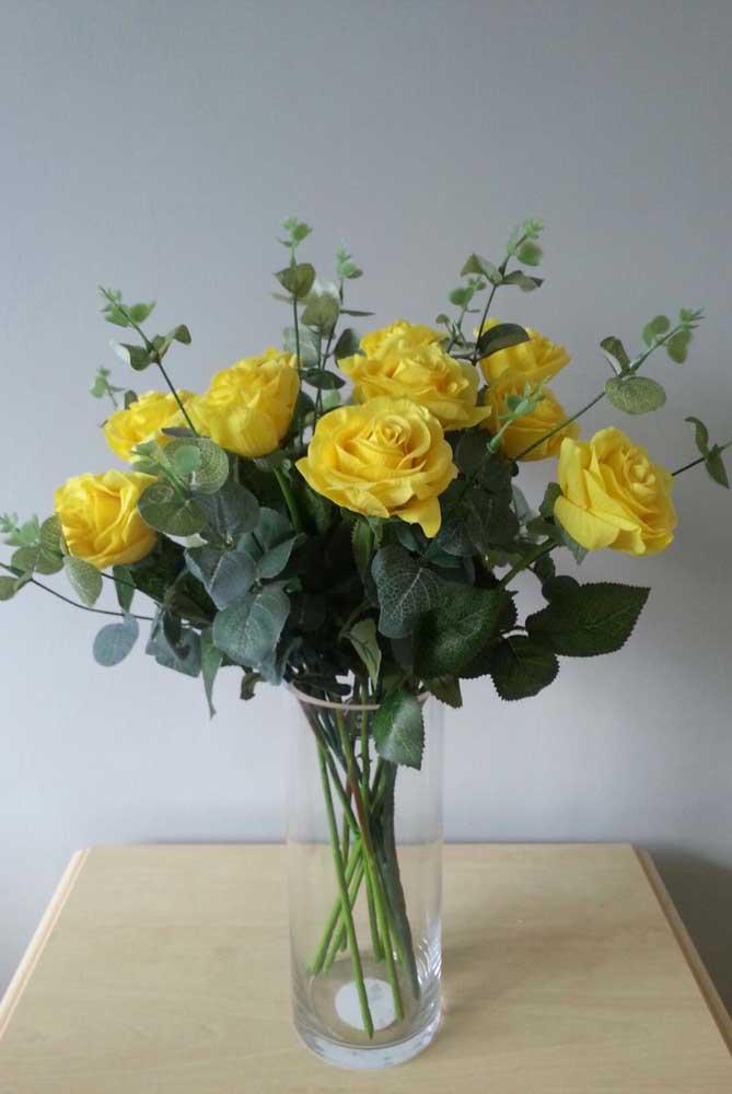 O arranjo de rosas amarelas forma um lindo contraste com as folhagens verde escuro