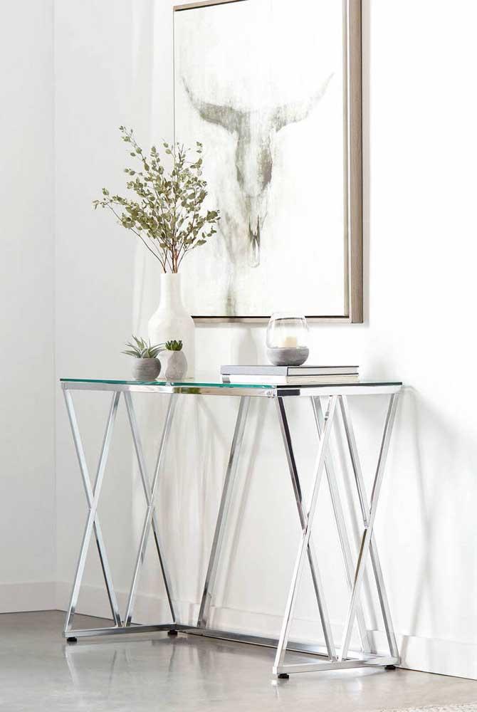 Aparador de vidro para uso decorativo. Destaque para o quadro perfeitamente proporcional ao tamanho do móvel