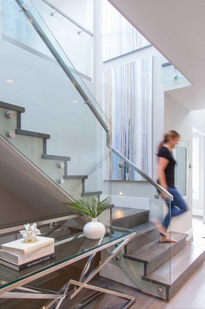 Aparador de vidro preenchendo o espaço embaixo da escada. Repare que o móvel casa direitinho com o guarda corpo no mesmo material