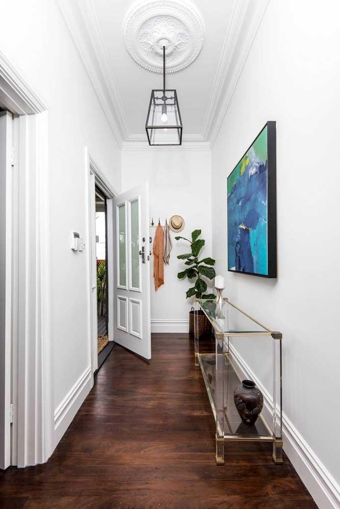 Aparador de vidro preenchendo e decorando o corredor. Repare que o móvel se encaixa perfeitamente no espaço