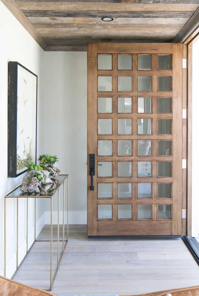 O hall de entrada rústico apostou em um aparador de vidro para criar contraste