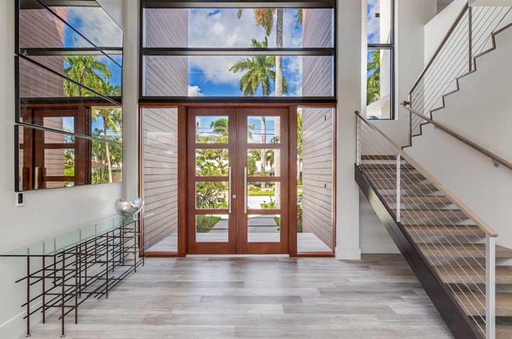 Um aparador de vidro proporcional a beleza e ao tamanho do hall de entrada