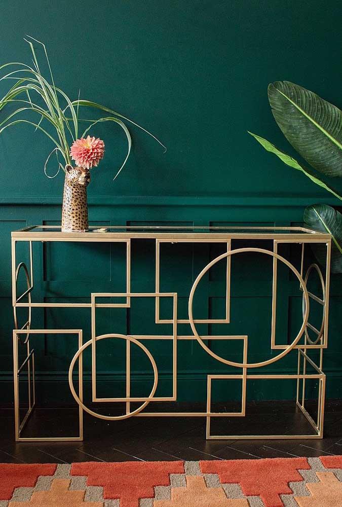 Aparador com tampo de vidro e estrutura metálica. O charme aqui está na composição entre o móvel e a parede verde