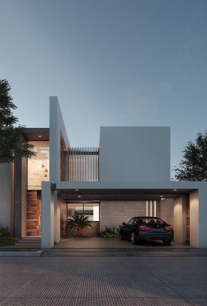 Fachada de casa moderna pintada de cinza e complementada pelos detalhes em madeira e pedra