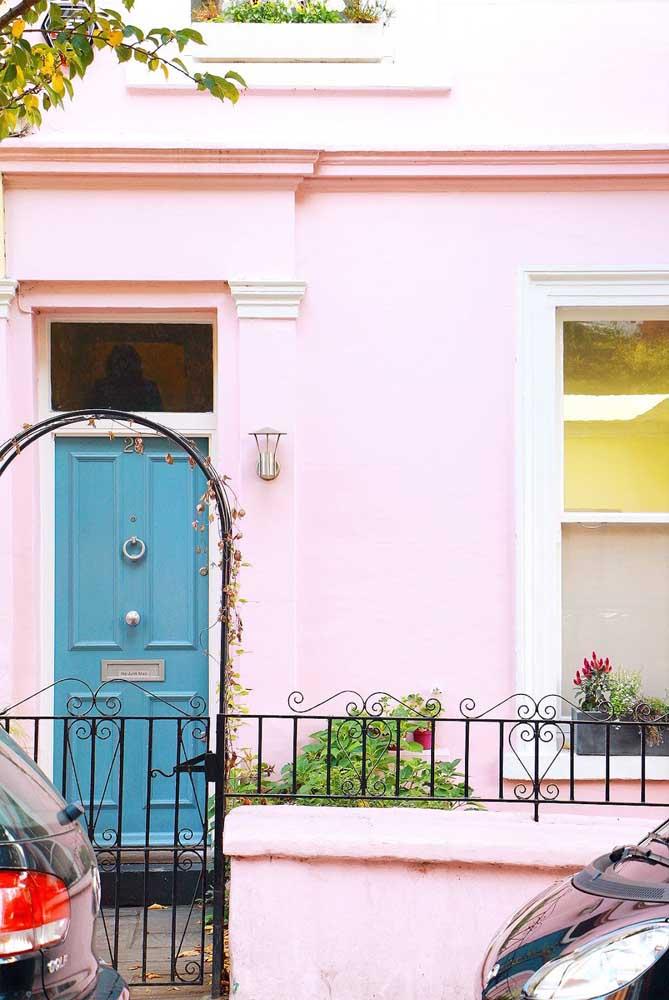 Uma romântica e delicada casa cor de rosa. A porta azul, no entanto, vem para trazer um toque de contemporaneidade