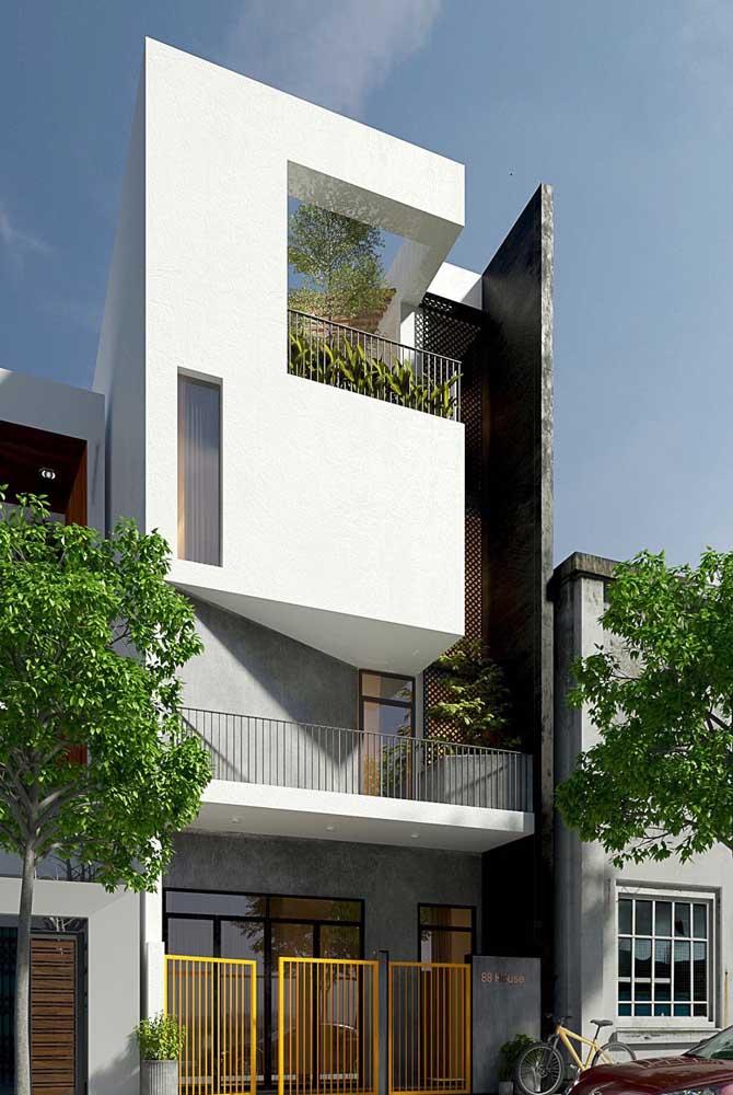 Combinação de branco e cinza para essa fachada de casa moderna. As pinceladas de amarelo garantiram um toque de descontração ao projeto