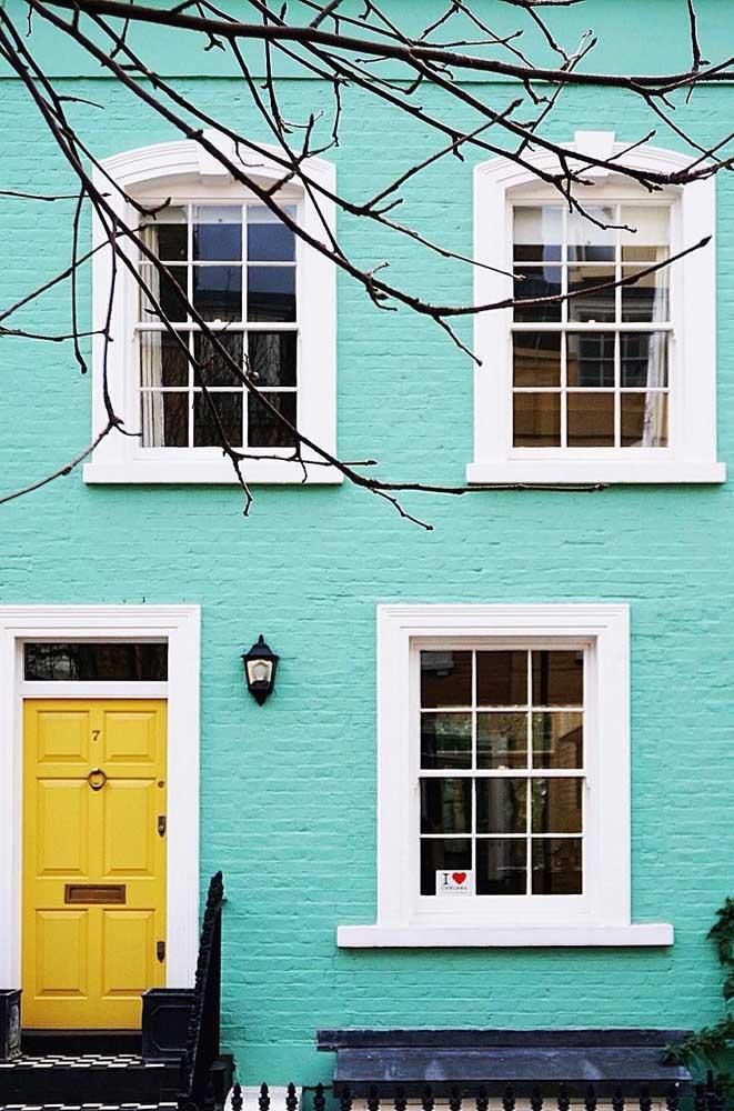 A casa antiga ganhou cor e vida com as paredes azuis e a porta amarela chamando toda atenção para si. As molduras brancas trazem leveza ao projeto
