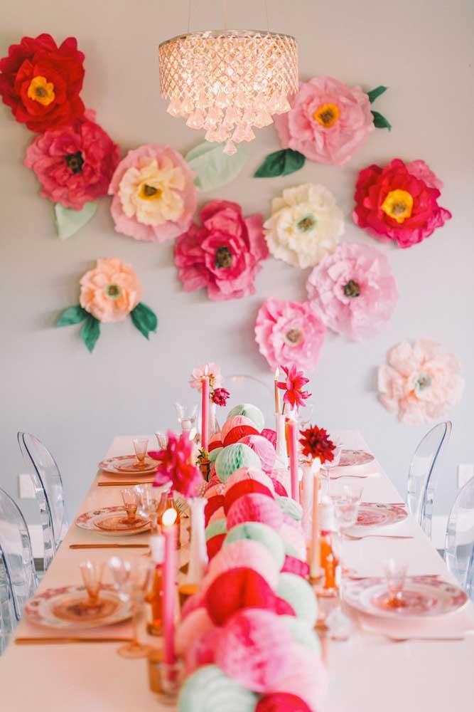 Nesse jantar de gala, as flores de papel de seda formam o painel na parede. Já sobre a mesa foram usados pompons, também de papel de seda