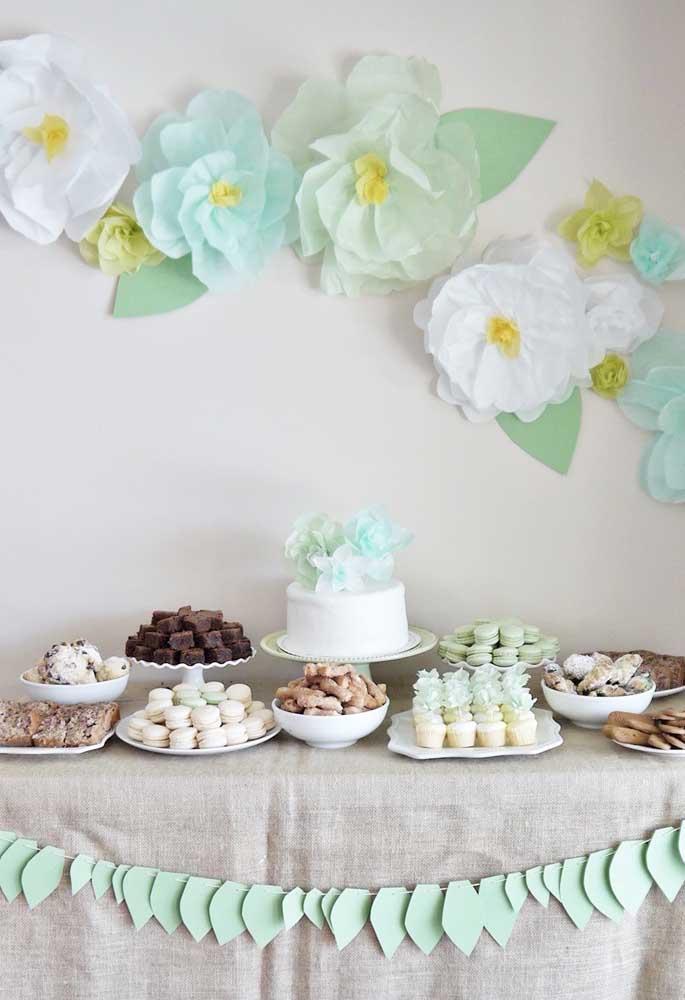 Em tons de branco e verde, as flores de papel de sede complementam a decoração da mesa do bolo