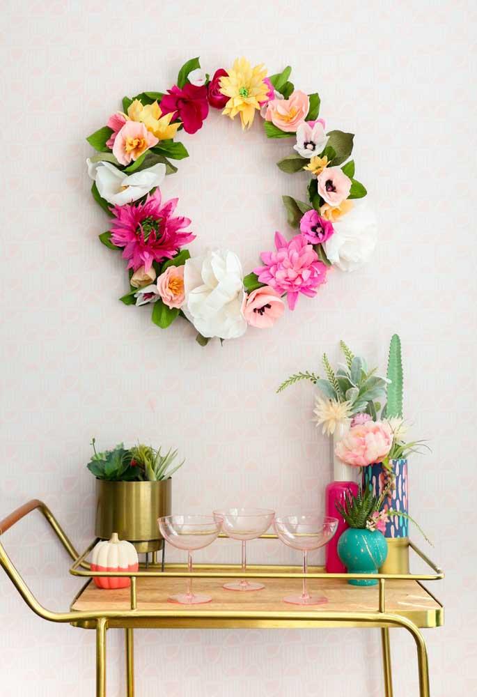 Essa linda guirlanda feita com flores de papel de seda ornamenta a parede do home bar. Mas também poderia decorar a porta, alguma outra parede ou o painel de uma festa