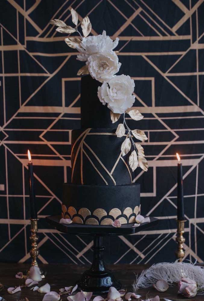 Bolo para o baile de máscaras decorado com pasta americana preta e flores brancas. Os detalhes em dourado finalizam o doce