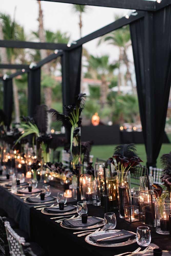 O clima de mistério prevalece nesse baile de máscaras decorado com velas e a cor preta
