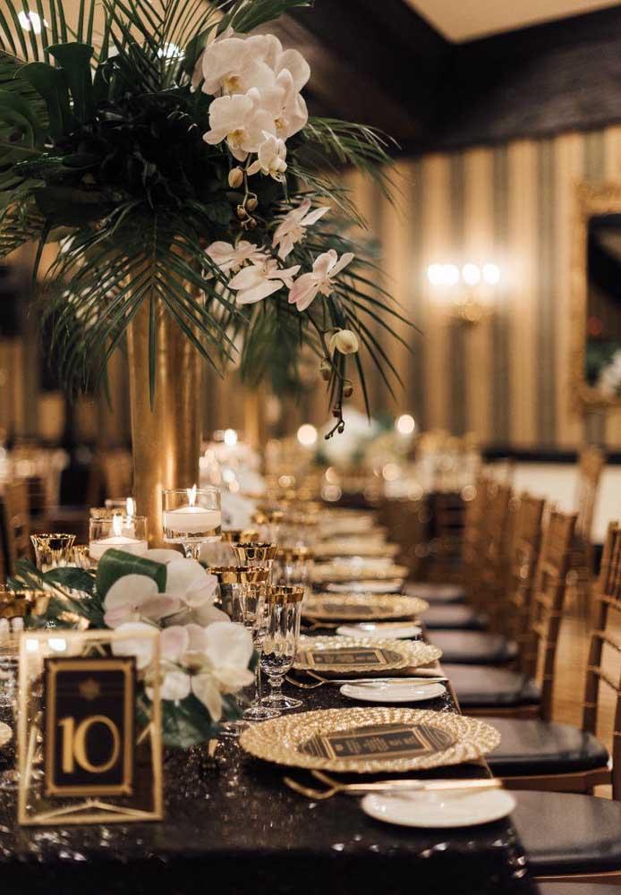 Flores e folhas tropicais decoram o centro de mesa desse elegante baile de máscaras
