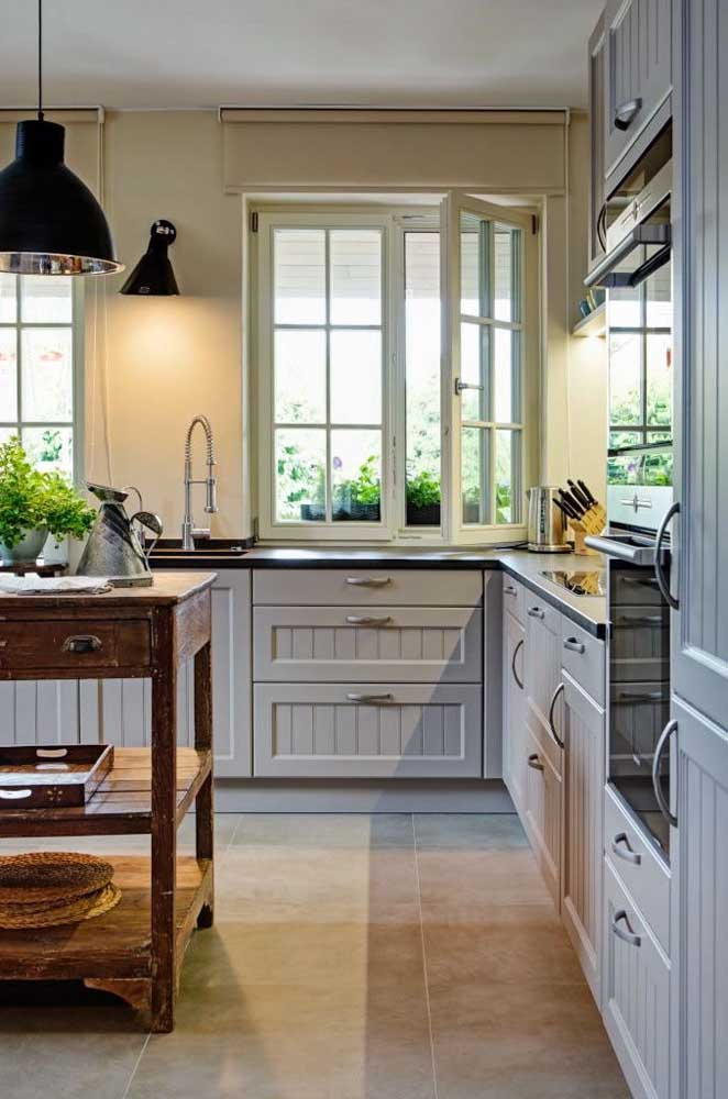 Nessa cozinha provençal, os armários cinzas ganharam molduras nas portas e para a ilha foi usado um armário de madeira antigo e desgastado