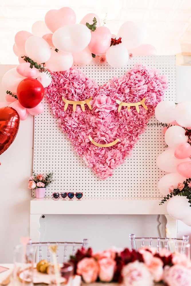 Aqui, é o coração feito com flores de papel e bexigas que se destacam