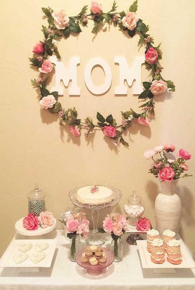 Olha que ideia mais simples e mais linda: painel de dia das mães feito com letras de papel e guirlanda de flores. Tudo colado diretamente na parede