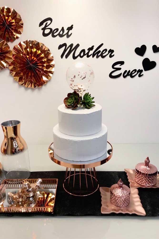 A mesa do bolo do dia das mães ganhou um painel feito diretamente na parede com enfeites de papel. Uma ideia simples, mas pra lá de bonita!