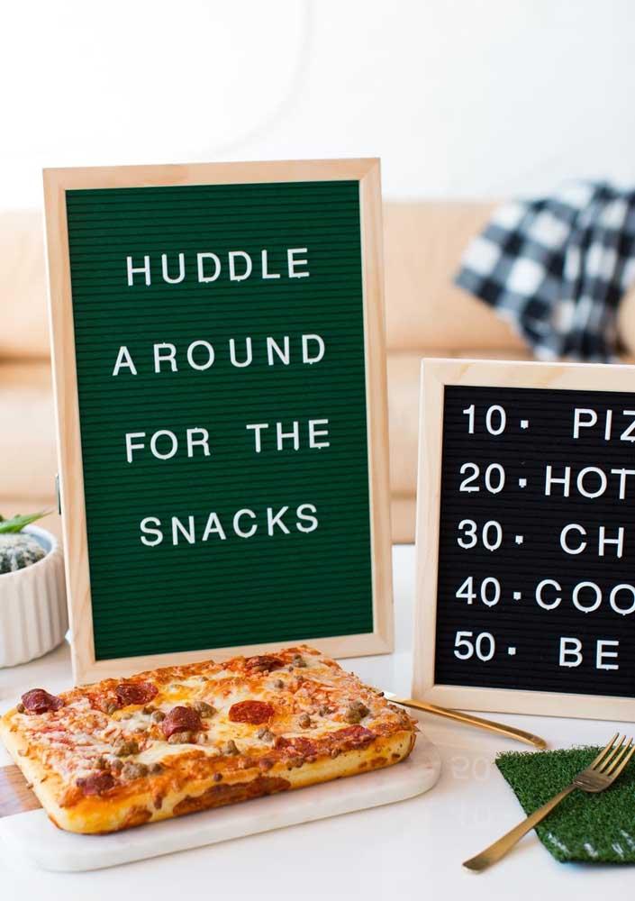 """Pizza para o intervalo do jogo. Destaque para o """"tapetinho"""" de grama sintética que apoia os talheres"""