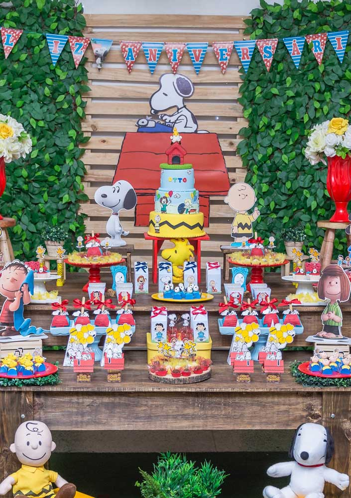 Mesa do bolo para Festa Snoopy. Destaque para o bolo fake com três andares e os totens dos personagens que ajudam a caracterizar a festa