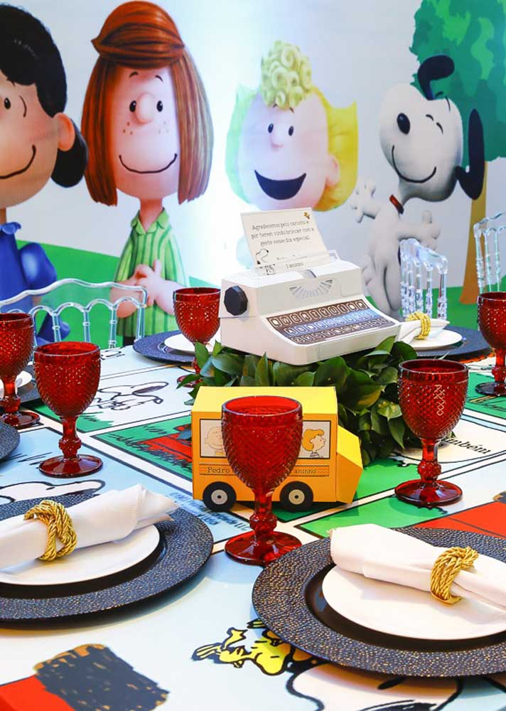 A ideia aqui é forrar a mesa da festa com os quadrinhos do Snoopy. Sobre a mesa, os objetos clássicos da história