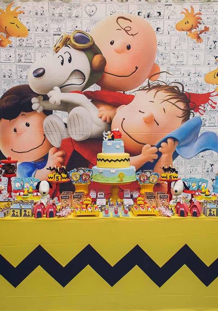 Um painel feito com os quadrinhos da turma do Snoopy emolduram essa colorida e divertida mesa de bolo